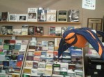 Assortment of books by local authors for purchase in the Bear Gallery with whimsical bird in the foreground