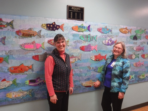 Kathy and Mary with plaque at fish mural naming ceremony no 2 on 3_9_17