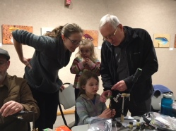A young fly tyer gets some instruction during a free community workshop on fly tying during the Feathers and Fingertips exhibition